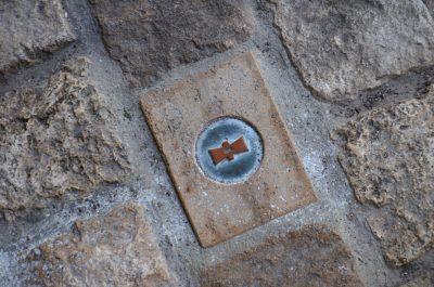 Ein Stein im Pfleaster unter dem Ratssaal markiert den Mittelpunkt der Stadt.